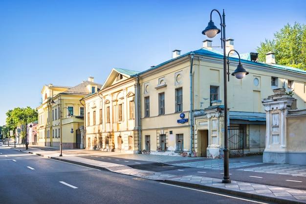 Vecchi edifici di palazzi gialli sulla via pyatnitskaya a mosca e lanterne in una mattina di sole estivo. iscrizione: via pyatnitskaya