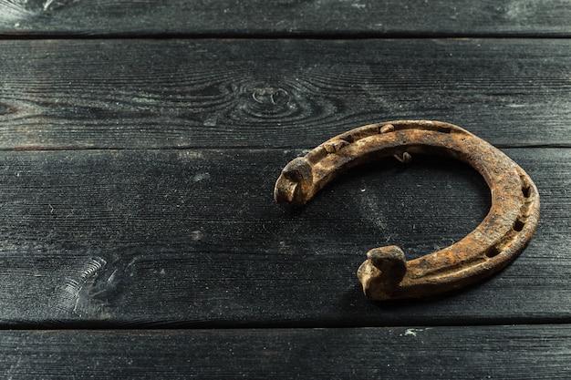 Vecchi ferri di cavallo arrugginiti sul bordo di legno