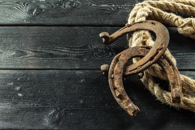 Vecchi ferro di cavallo e corda su fondo di legno