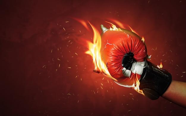Vecchi guantoni da pugile rossi sul fondo caldo delle scintille con la fiamma estrema del fuoco e la lotta ferocemente della mano per il concetto di successo o del vincitore.