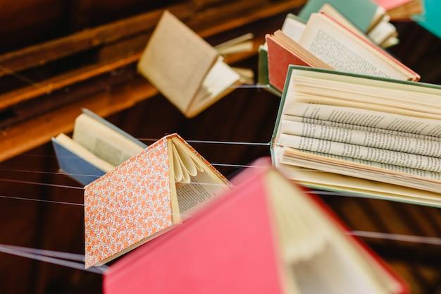 Vecchi libri appesi a stringhe per incoraggiare la lettura e conoscere la cultura.