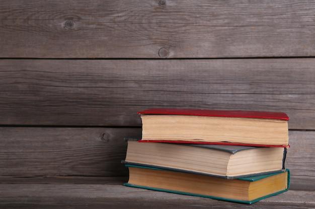 Vecchi libri d'annata sulla tavola di legno grigia