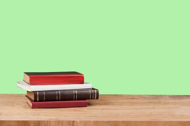 Vecchi libri di testo sulla tavola di legno di lerciume con il fondo di colore.