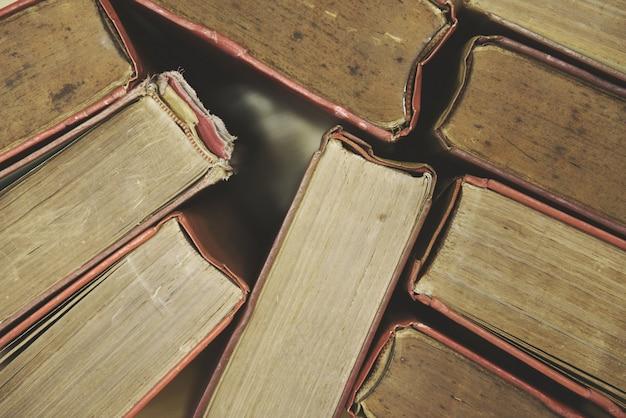 Vecchi libri sui mucchi del libro della libro con copertina rigida di vista superiore del pavimento di legno nella stanza delle biblioteche e nei precedenti di istruzione di nuovo alla scuola