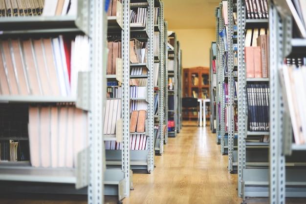 Vecchi libri sul fondo dello scaffale per libri - pila di libri nella stanza delle biblioteche per l'affare e l'istruzione