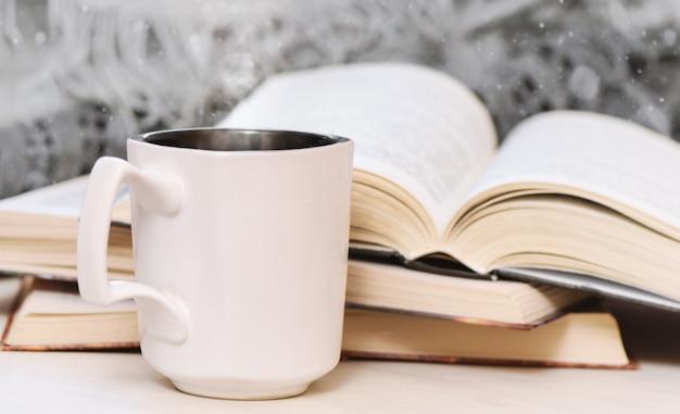 Vecchi libri sulla tavola e sulla tazza di caffè di legno.