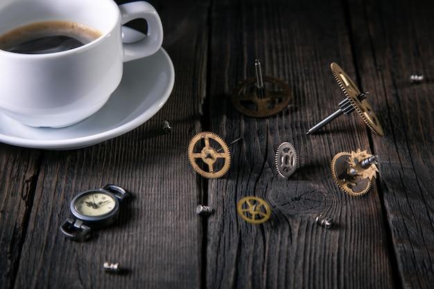 Vecchi orologi, ingranaggi, viti, una tazza di caffè incompiuto su assi di legno.