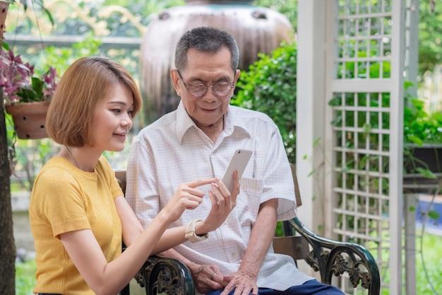 Vecchi padre e figlia asiatici. la figlia insegna a un padre anziano di usare un telefono cellulare