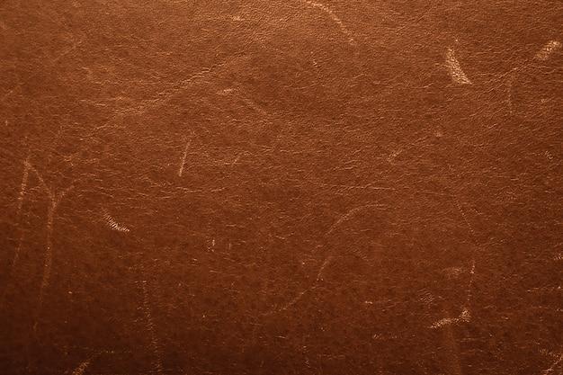 Vecchi pellami marroni graffiati. texture vintage in pelle, superficie danneggiata, sfondo grunge. materiale malandato esposto all'aria.