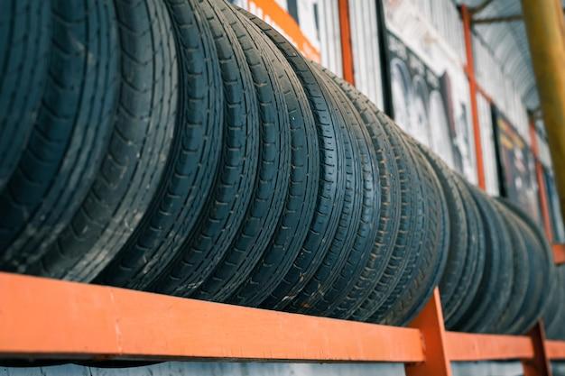 Vecchi pneumatici che sono allineati sul supporto per pneumatici