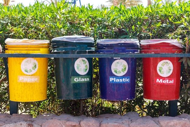 Vecchi recipienti di riciclaggio variopinti nel parco. urne per la raccolta differenziata dei rifiuti