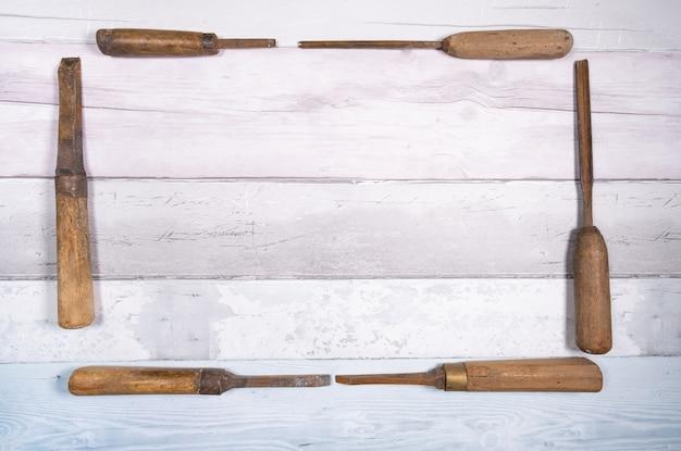 Vecchi scalpelli di legno che formano una cornice su uno sfondo di vecchie schede. vista dall'alto con spazio per il testo