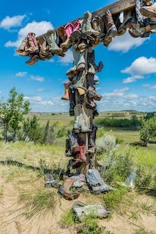 Vecchi stivali da cowboy che appendono su una posta nel great sandhills nel saskatchewan, canada