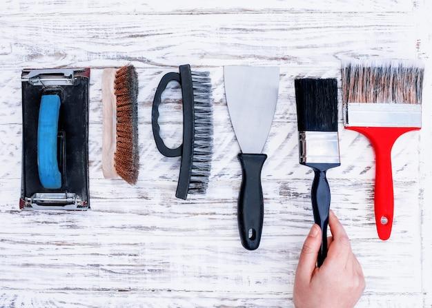 Vecchi strumenti (pennelli, spatola, spazzola metallica, portarotolo di carta vetrata) e mano prendendo uno brus uno sul bordo bianco