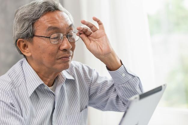 Vecchi uomo anziano anziano asiatico felice usando esaminando lo schermo del ridurre in pani per comunicare con l'altro.