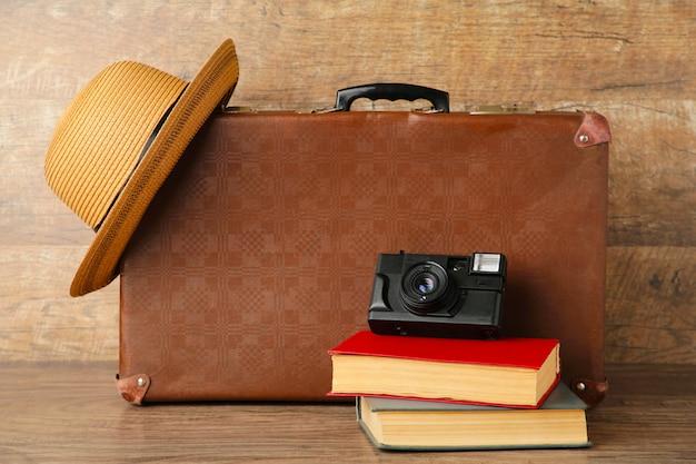 Vecchi valigia e libri con la macchina fotografica sulla parete marrone
