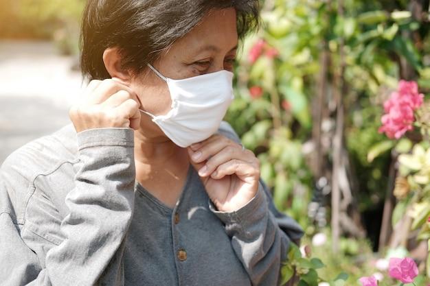 Vecchia asiatica che indossa una maschera di stoffa bianca per prevenire il virus covid-19 o corona in thailandia e protezione per l'inquinamento atmosferico valore 2,5