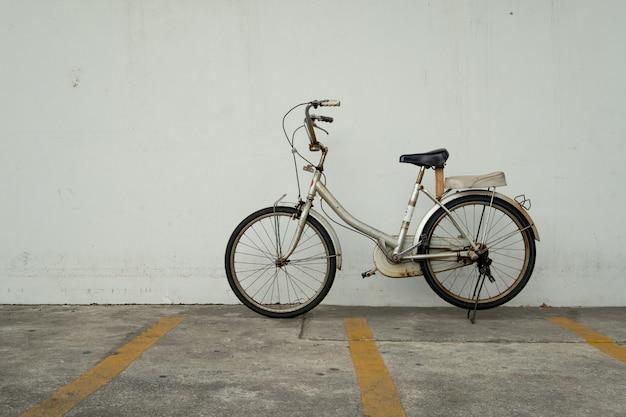 Vecchia bicicletta d'annata arrugginita al parcheggio della bicicletta. concetto di stile di vita eco-friendly e urbano.
