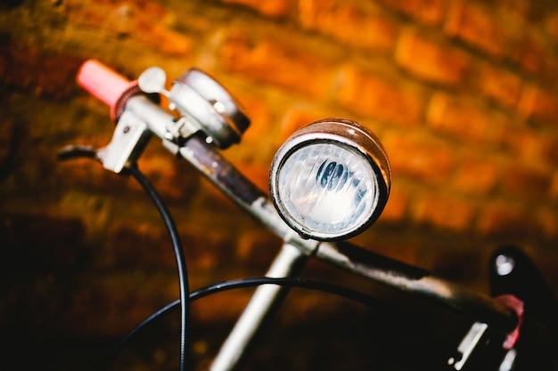 Vecchia bicicletta d'annata arrugginita vicino al muro di cemento