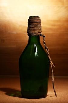 Vecchia bottiglia su superficie di legno