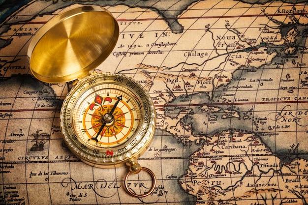 Vecchia bussola dorata d'annata sulla mappa antica