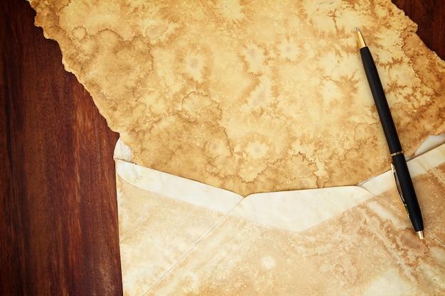 Vecchia busta dell'annata di carta isolata su fondo di legno