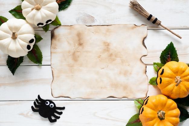 Vecchia carta con zucche fantasma giallo sul bordo di legno. concetto di halloween.