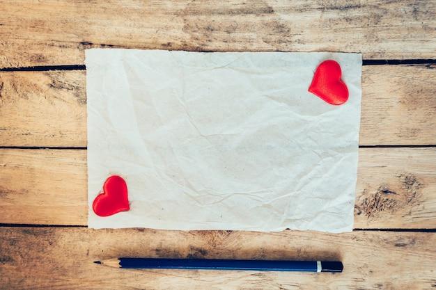 Vecchia carta e cuore rosso con matita su sfondo di legno per biglietto di auguri di san valentino.