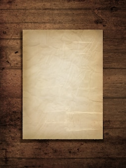 Vecchia carta macchiata su una priorità bassa di legno del grunge