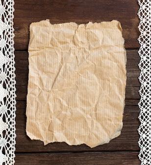 Vecchia carta su un fondo di legno marrone con una certa decorazione