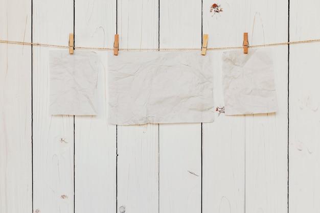 Vecchia carta vuota appesa su sfondo bianco di legno con spazio per il testo.