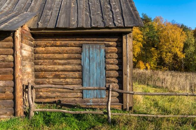 Vecchia casa di campagna fatta di tronchi. porta di legno al cortile. una recinzione fatta di travi in legno.