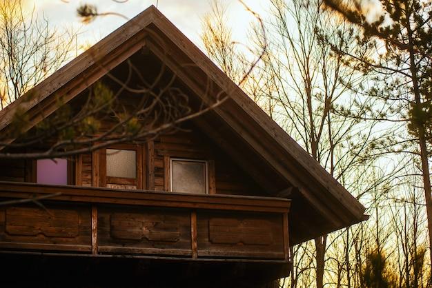 Vecchia casa di legno al tramonto con una piccola luce solare in primavera.