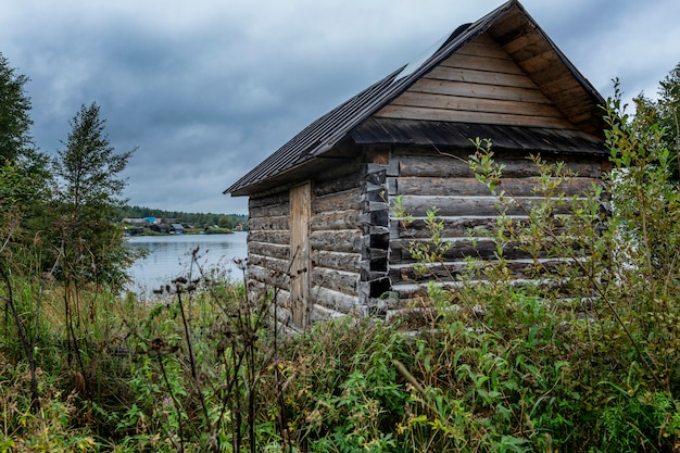 Vecchia casa di legno in un boschetto di erba dal fiume.