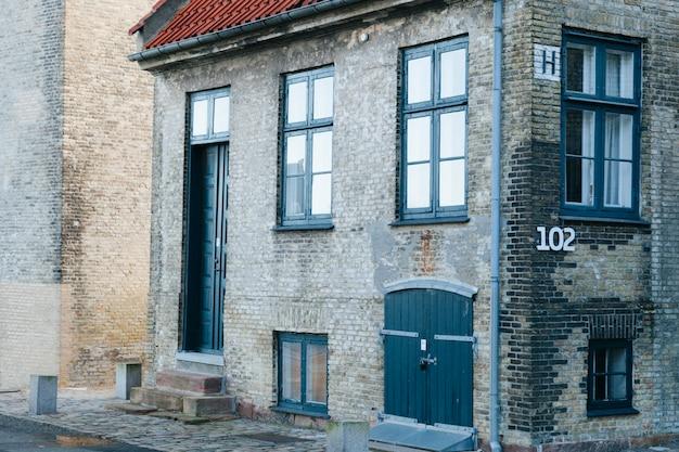 Vecchia casa di mattoni su strada asfaltata