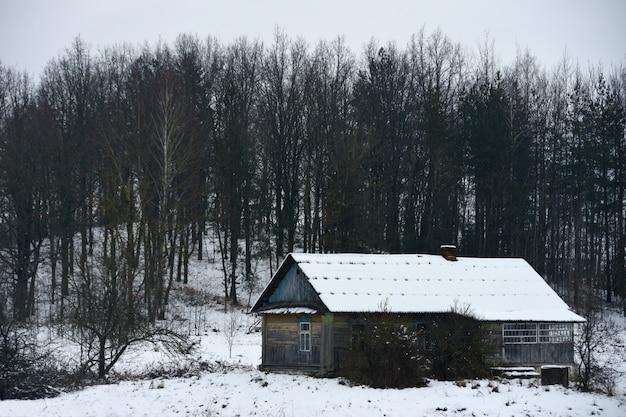 Vecchia casa nella foresta invernale