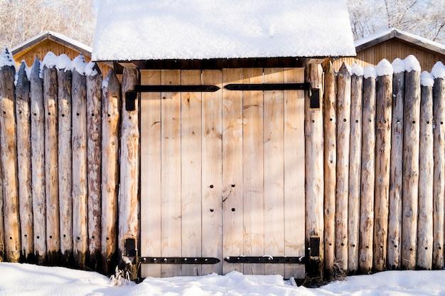 Vecchia casa nella foresta siberiana recintata con neve palizzata