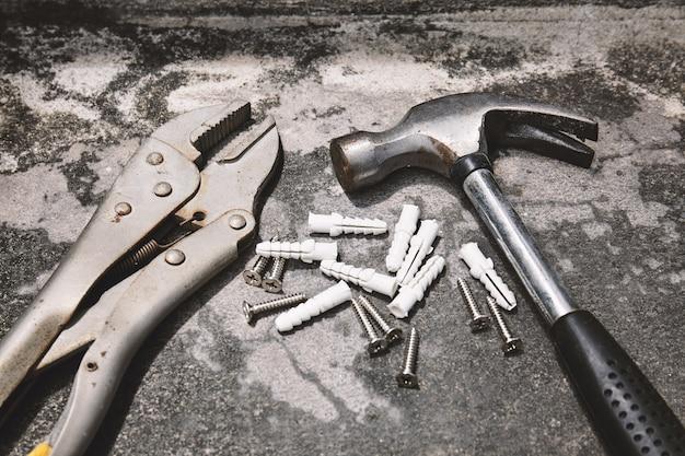Vecchia chiave d'acciaio, martello con ancore di plastica sul fondo del cemento