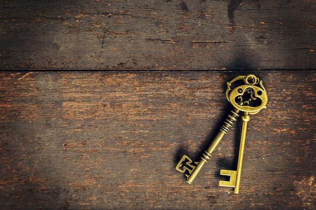 Vecchia chiave dell'annata su sfondo della trama di legno con spazio