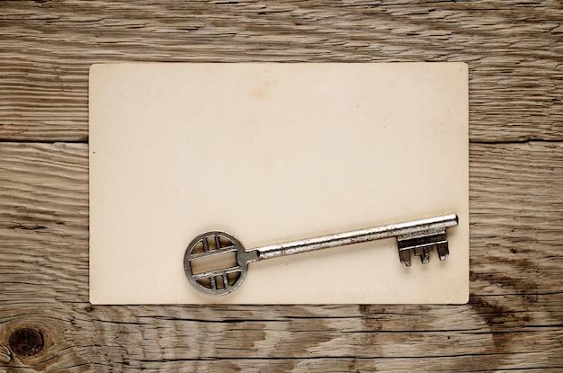Vecchia chiave e cartolina su legno