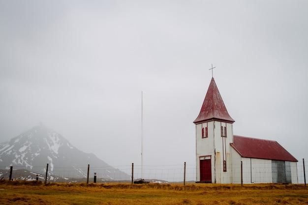 Vecchia chiesa con un tetto rosso in un campo sotto un cielo nuvoloso in islanda