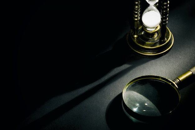 Vecchia clessidra vintage con lente d'ingrandimento con ombra su sfondo scuro