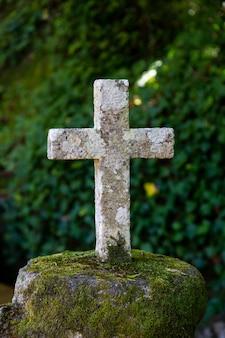 Vecchia croce cattolica di pietra nella foresta