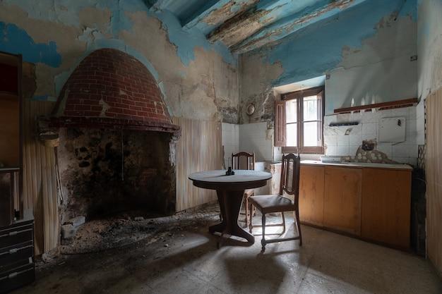 Vecchia cucina con camino di una casa abbandonata