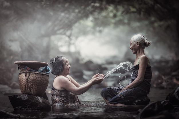 Vecchia donna asiatica in cascata