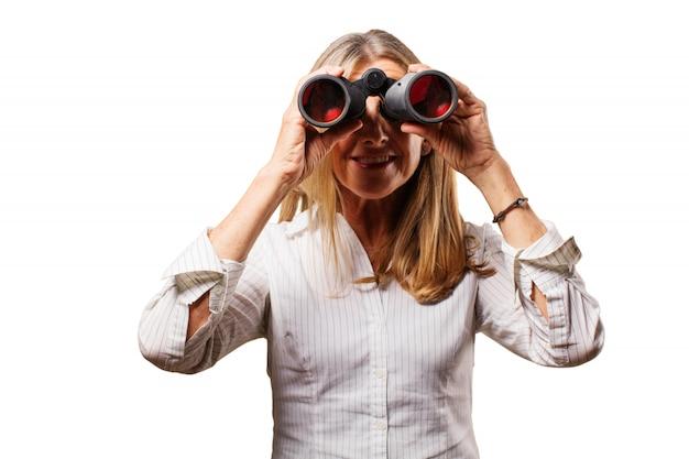 Vecchia donna guardando attraverso un binocolo