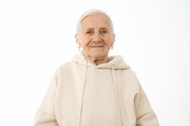 Vecchia donna in felpa con cappuccio beige con airpods bianchi nelle orecchie