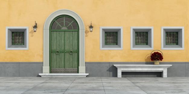 Vecchia facciata con porta in legno, finestre e panca