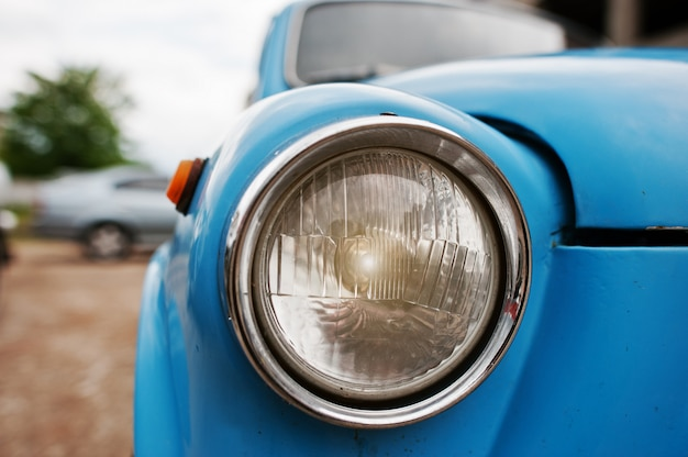 Vecchia fine d'annata del faro dell'automobile su all'automobile blu.
