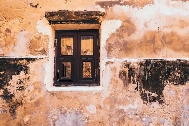 Vecchia finestra di legno bianca di tono d'annata sui precedenti gialli rustici della facciata del muro di cemento